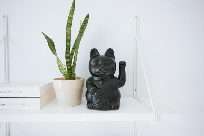 Чёрный кот манеки-неко с поднятой левой лапой